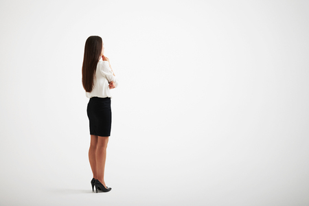 Young girl with long hair and wearing formal clothes touches to her chin, back view Stock Photo