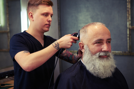 bushy: Concentrated skillful barber making haircut to handsome attractive senior man with beard and working with electric razor