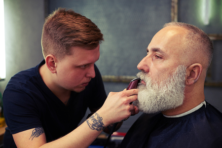 man style: Young barber with tattoo shaving beard of his client with hair clipper in hair salon