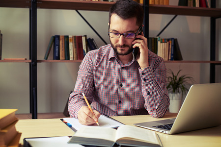 Uomo serio con gli occhiali che fanno note mentre parla al telefono