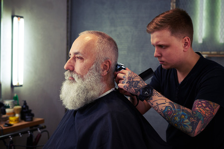 bushy: Young concentrated skillful barber making perfect hear to handsome bearded man using trimmer and comb in hair salon