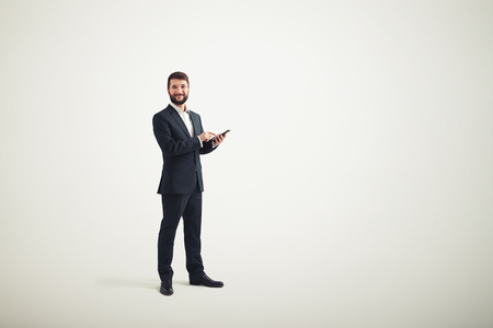 formal wear clothing: A smiling businessman in a formal wear with black phone in his hands Stock Photo