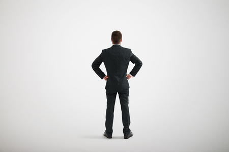 arms akimbo: Back view of standing man in a formal clothes with his hands akimbo