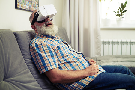 looking around: Senior Caucasian man looking around using white virtual reality headset glasses Stock Photo
