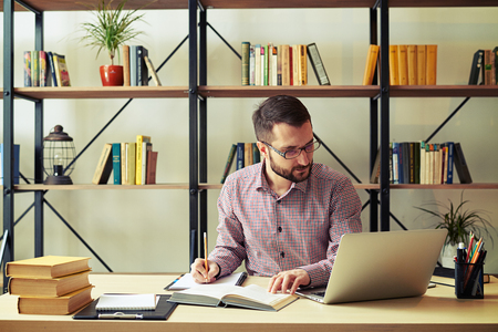 rewriting: Attractive young businessman with the glasses rewriting from a book and looking at his laptop