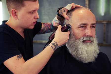 hair style: Barber with tattoo making haircut to hipster senior man with beard and working with electric razor