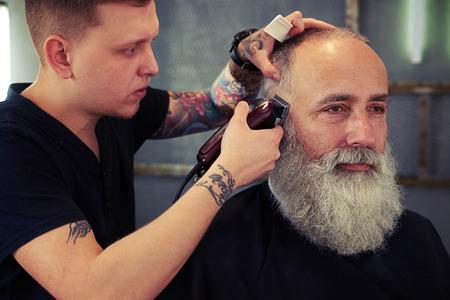 Kapper met tattoo maken kapsel naar hipster senior man met baard en werken met elektrische scheermes Stockfoto