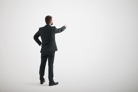 Back view of man standing and pointing his finger forward wearing formal wear
