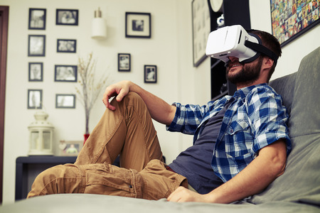 caucasian: Young Caucasian man resting on comfortable sofa wearing VR headset glasses