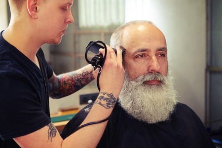 electric razor: Barber making haircut to handsome attractive senior man with beard and working with electric razor Stock Photo