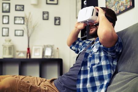 Young Caucasian man holding virtual reality headset glasses and smiling