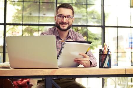 notebook computer: Smiling businessman with glasses looking at camera and taking notes in his home office Stock Photo