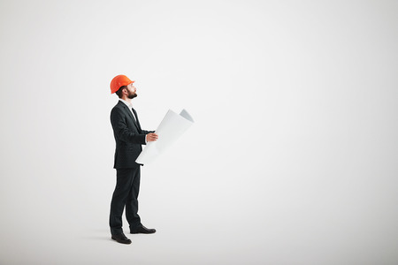 looking upwards: Side view of bearded man in a formal wear and in a hard hat holding blueprints and looking upwards Stock Photo