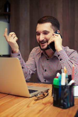 busy beard: Satisfied young businessman talking on phone and gesticulating in his home office