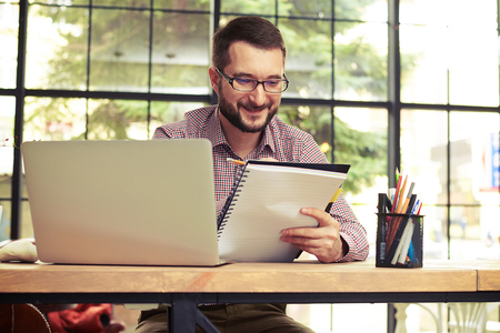 busy beard: Smiling businessman with glasses sitting behind a table with his laptop and taking notes Stock Photo