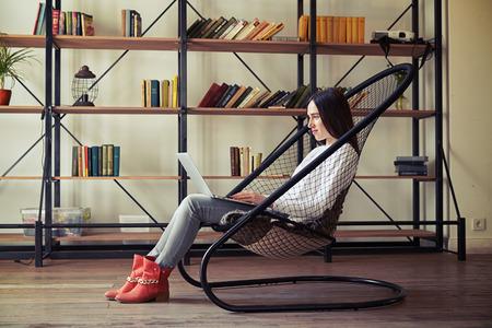 silla de madera: La mujer joven está sentado en una silla de red y trabajo en su portátil en casa, en el fondo de los estantes