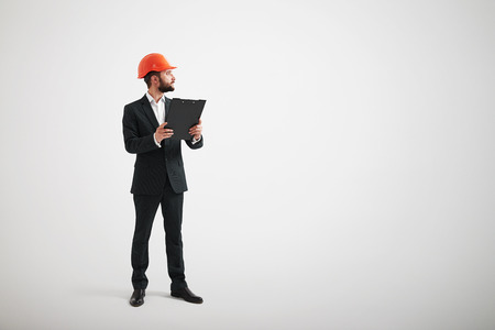 calzado de seguridad: Adult Caucasian man in a black suit and construction helmet looking to the side and holding black folder