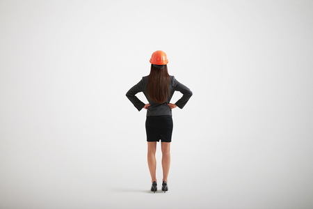 arms akimbo: Back view of woman in formal wear and construction helmet with her arms akimbo