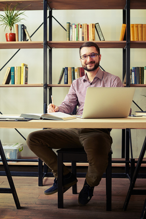 casual office: Smiling young businessman with the glasses sitting on a chair taking notes and using his laptop
