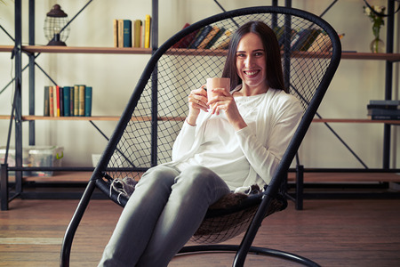 designer chair: Young caucasian brunette with wide smile sitting in a designer chair with a cup