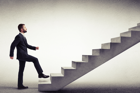Jeune homme de race blanche dans une usure début officiel à monter les escaliers en béton, vue latérale