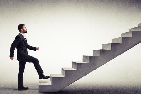Jonge blanke man in een formele slijtage start klimmen betonnen trap, zijaanzicht