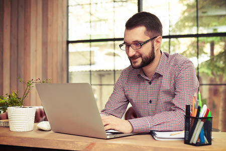 busy beard: Happy businessman with glasses typing on his laptop in his home office