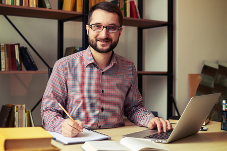 rewriting: Close up of smiling young businessman with the glasses who rewriting from his laptop Stock Photo