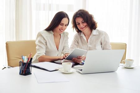 mujeres juntas: Dos sonriendo a las mujeres jóvenes que trabajan junto con aparatos de ellas muestra otra cosa en la tableta en la oficina moderna Foto de archivo