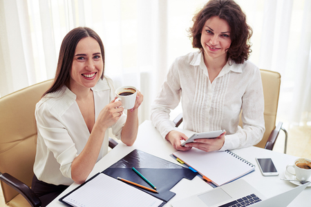 teamworking: Two young smiling women teamworking with gadgets and drinking coffee  in the modern office