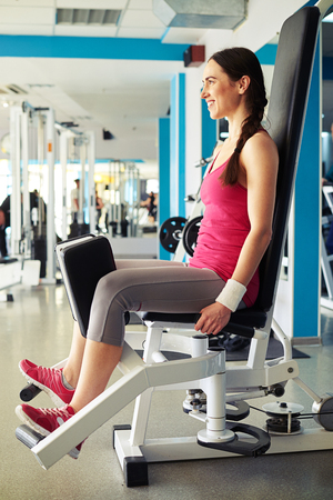 abductor: Young beautiful Caucasian smiling girl is working out on hip abductor machine in gym
