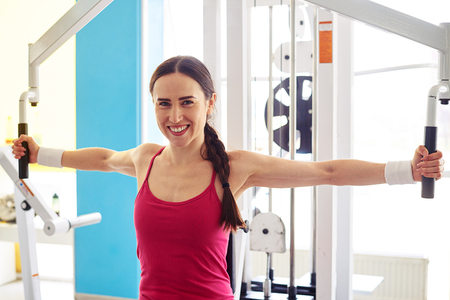 femme papillon: Pretty Caucasian smiling woman is working out on butterfly machine in gym