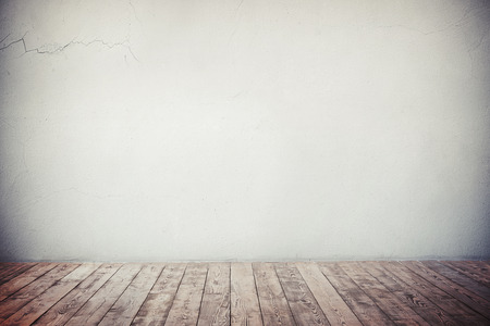 vignetting: Empty grey wall with cracks and natural brown wooden floor, with strong vignetting