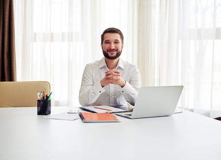 man working computer: Beard smiling man sitting at the big white table and crossed his fingers in the modern white office