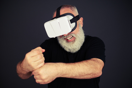 smother: Senior man clenches his fists and his teeth in virtual reality wearing hi-tech VR headset