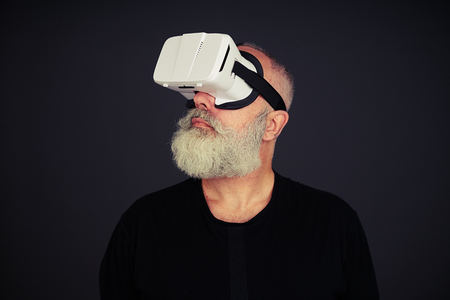 looking around: Senior man looking around using virtual reality glasses, on black background