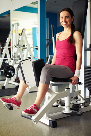 abductor: Young Caucasian smiling woman is working out on hip abductor machine in gym Stock Photo