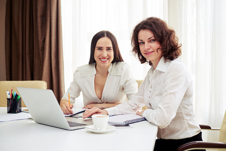 mujeres juntas: Dos mujeres jóvenes sonriendo teamworking en la mesa y mirando directamente en la cámara