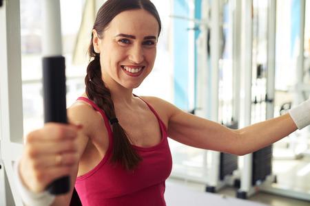 mujer bonita: sonriente mujer de raza caucásica bastante joven está trabajando en el gimnasio