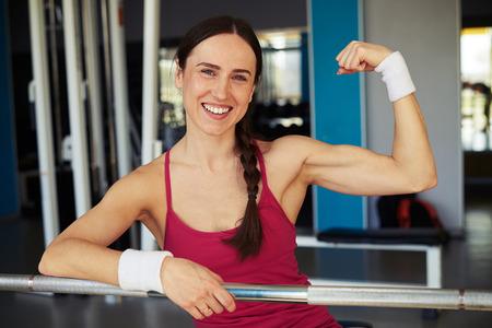 Sonriente mujer de mostrar sus bíceps en club de deporte y se aferra a la barra en el club de deporte Foto de archivo