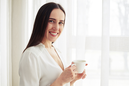 white woman: Young smiling pretty woman stands and holding coffee  indoor
