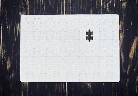 work piece: Jigsaw white puzzle with one last missing piece on wood Stock Photo