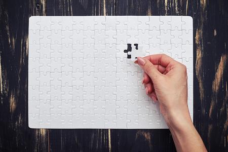 missing puzzle piece: Last puzzle piece on dark wooden desk