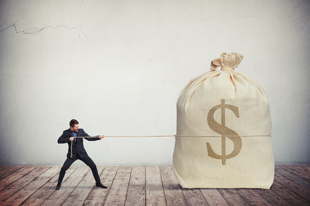 pulling money: Man pulling on a rope big bag of money, grey wall on background Stock Photo