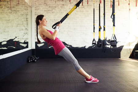Young smiling girl in sportswear is pushing at the trx Foto de archivo