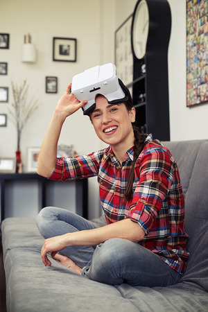 hand position: Smiling young woman sitting on the sofa in the lotus position, holding virtual reality glasses in the right hand