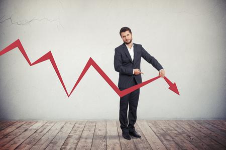 Deluso imprenditore che punta a grafico rosso freccia verso il basso.
