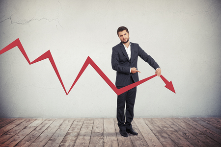 Teleurgesteld zakenman wijst naar rode grafiek pijl naar beneden.