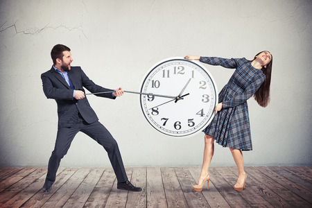 dress suit: A young woman in checkered dress is intensively holding the big round clock while the man in dark business suit is pulling an hour-hand as if trying to slow down the time