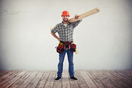 A young bearded workman in casual clothes, hard hat and utility belt is holding some wooden boards on his shoulder